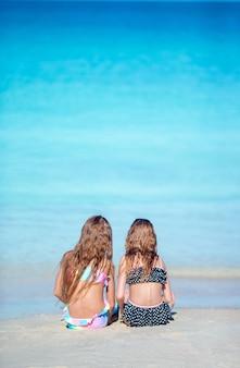Entzückende kleine mädchen, die mit sand auf dem strand spielen. hintere ansicht von den kindern, die im seichten wasser sitzen und eine sandburg machen