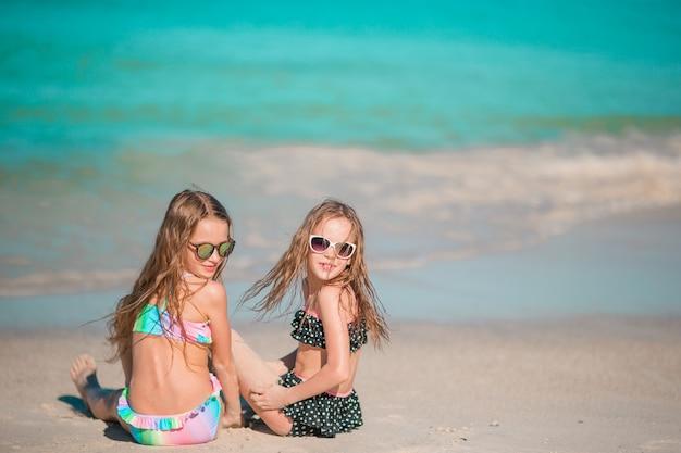 Entzückende kleine mädchen, die mit sand auf dem strand spielen. kind sitzt im seichten wasser
