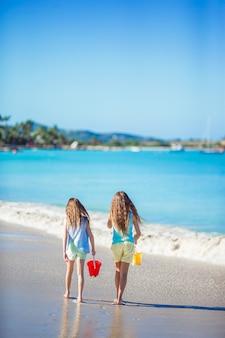 Entzückende kleine mädchen, die mit sand auf dem strand spielen