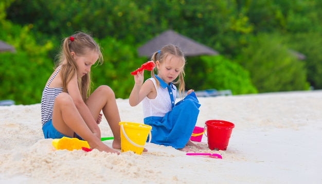 Entzückende kleine mädchen, die mit strandspielwaren spielen
