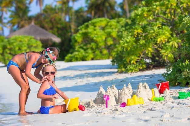 Entzückende kleine mädchen, die mit strandspielwaren während der tropischen ferien spielen