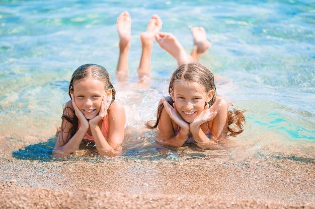 Entzückende kleine mädchen, die spaß am strand im seichten wasser haben
