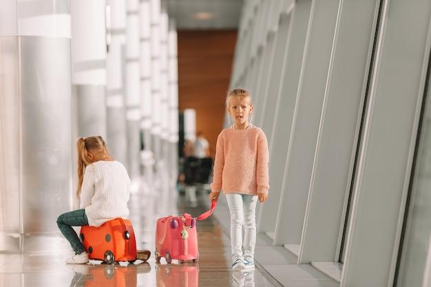 Entzückende kleine mädchen, die spaß im flughafen sitzt auf kofferwartebord haben