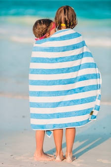 Entzückende kleine mädchen eingewickelt im tuch am tropischen strand