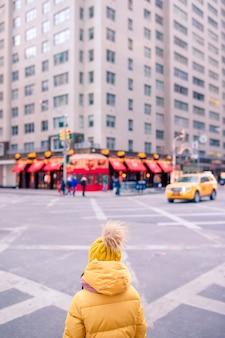Entzückende kleine mädchen haben spaß am times square in new york city