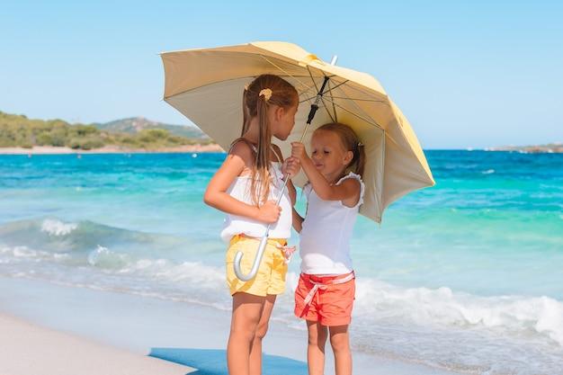 Entzückende kleine mädchen haben spaß zusammen am strand mit regenschirm