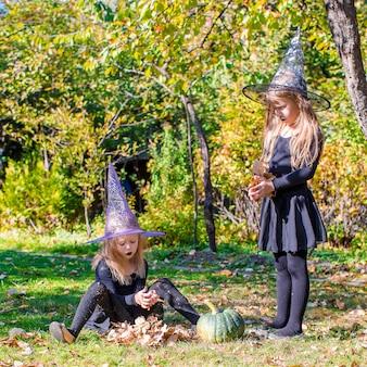 Entzückende kleine mädchen im hexenkostüm an halloween draußen