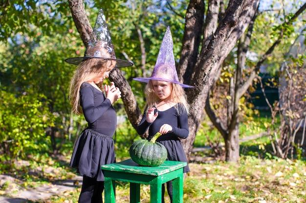 Entzückende kleine mädchen im hexenkostüm an halloween haben spaß