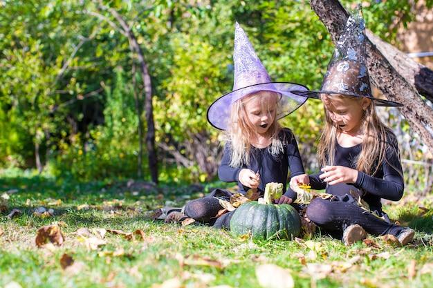Entzückende kleine mädchen im hexenkostüm, das einen bann auf halloween wirft