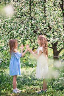 Entzückende kleine mädchen in blühendem apfelbaumgarten am frühlingstag