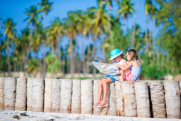 Entzückende kleine mädchen mit großer karte von insel auf strand