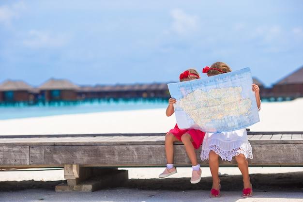 Entzückende kleine mädchen mit karte von insel auf strand
