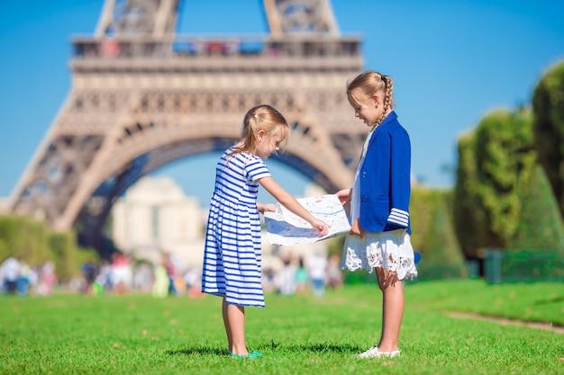 Entzückende kleine mädchen mit karte von paris-hintergrund der eiffelturm