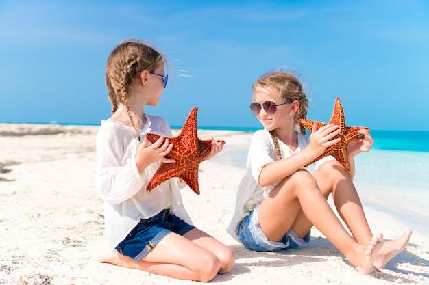 Entzückende kleine mädchen mit starfish auf weißem strand