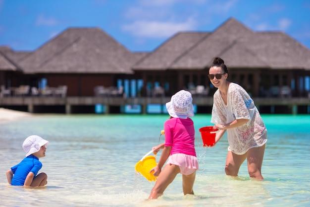 Entzückende kleine mädchen und glückliche mutter, die mit strandspielwaren auf sommerferien spielt