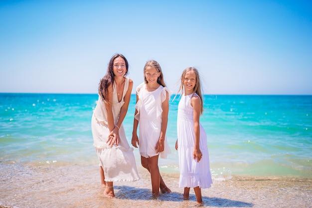 Entzückende kleine mädchen und junge mutter am tropischen weißen strand