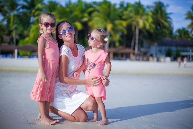 Entzückende kleine mädchen und junge mutter auf tropischem weißem strand