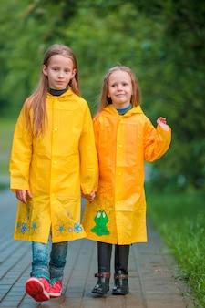 Entzückende kleine mädchen unter dem regen am warmen herbsttag