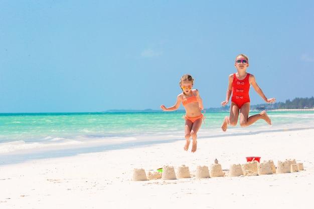 Entzückende kleine mädchen während der sommerferien. die kinder, die mit strand spielen, spielen auf dem weißen strand