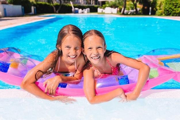 Entzückende kleine schwestern spielen im swimmingpool im freien