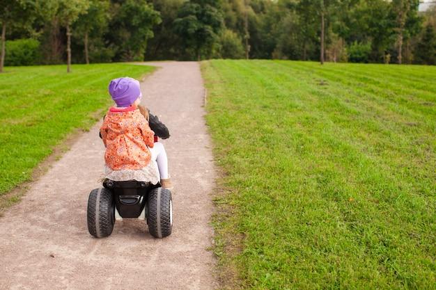 Entzückende kleine süße mädchen fahren draußen ein motorrad