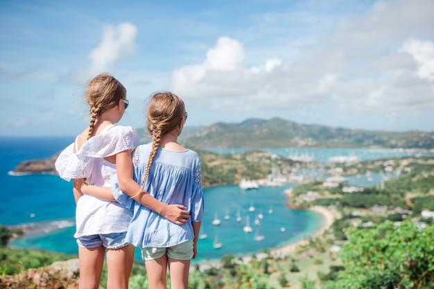Entzückende kleinkinder, welche die ansicht des malerischen englischen hafens in antigua im karibischen meer genießen