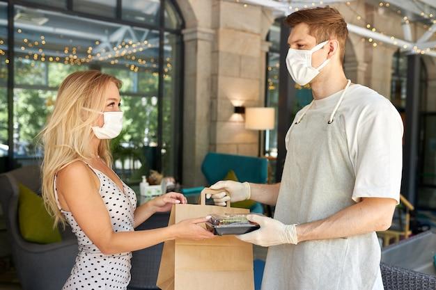 Entzückende kundin nimmt ihre bestellung im restaurant während des coronavirus entgegen