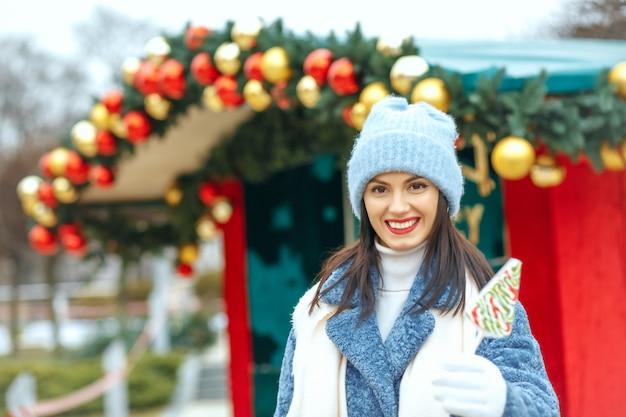Entzückende lächelnde frau, die süßigkeit am weihnachtsmarkt hält. leerer platz