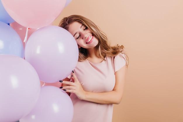 Entzückende langhaarige frau, die mit geschlossenen augen steht und partyballons hält