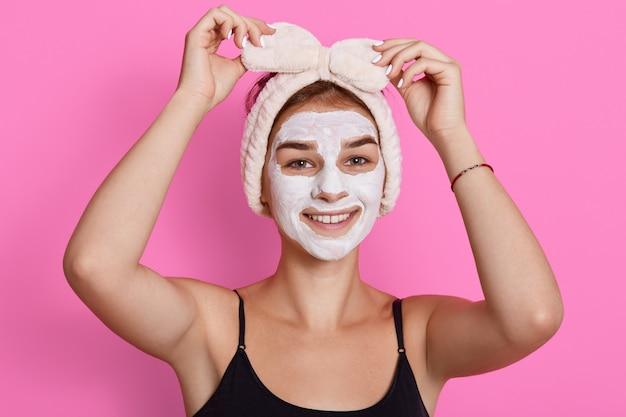 Entzückende lustige frau mit tonmaske auf ihrem gesicht und haarband mit schleife auf dem kopf, die ihr stirnband berührt, hat schönheitsverfahren zu hause am morgen.