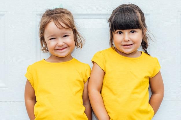 Entzückende mädchen, die ein gelbes hemd tragen, das gegen weißen hintergrund lehnt