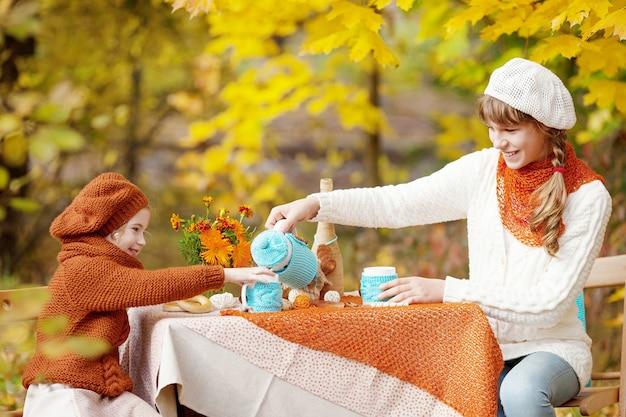 Entzückende mädchen, die teeparty draußen im herbstgarten haben