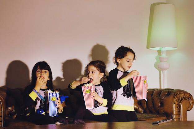 Entzückende mädchen, die zu hause popcorn genießen