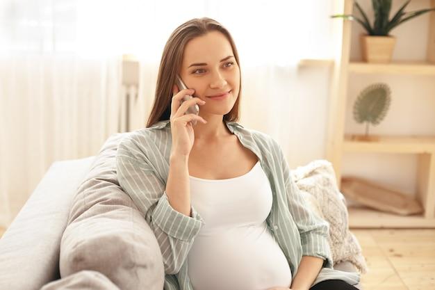 Entzückende niedliche junge schwangere frau, die aufwirft