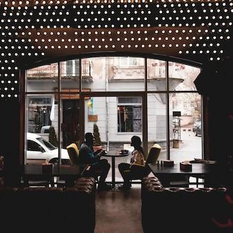 Entzückende paare, die im café sitzen