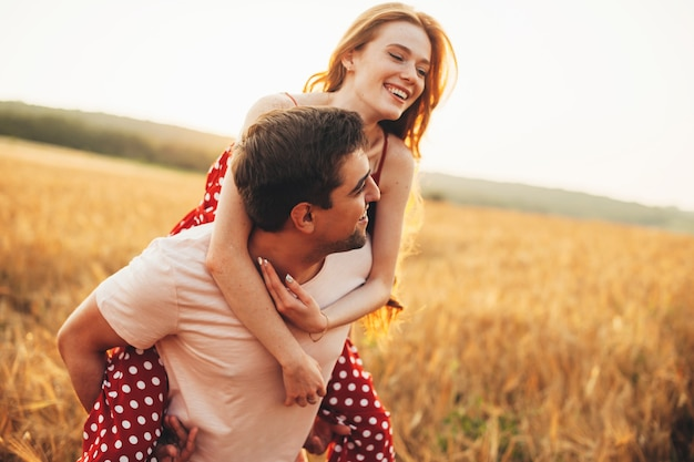 Entzückende paare spielen auf einem feld während eines sonnenuntergangs lächelnd und umarmend