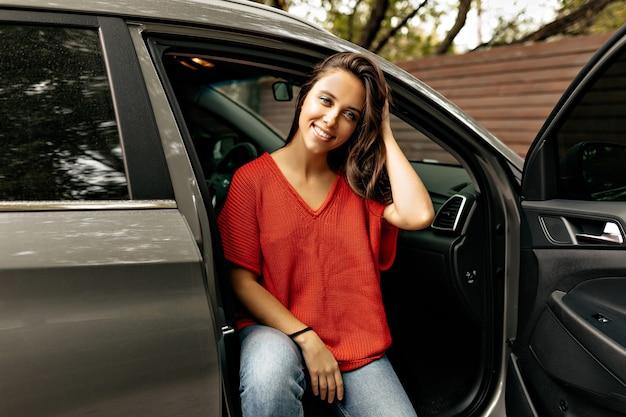 Entzückende reizende dame mit charmantem lächeln, das im auto sitzend aufwirft