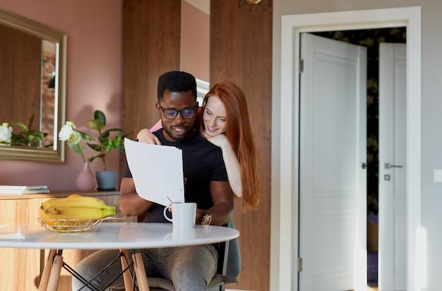 Entzückende rothaarige frau unterstützt arbeitenden ehemann