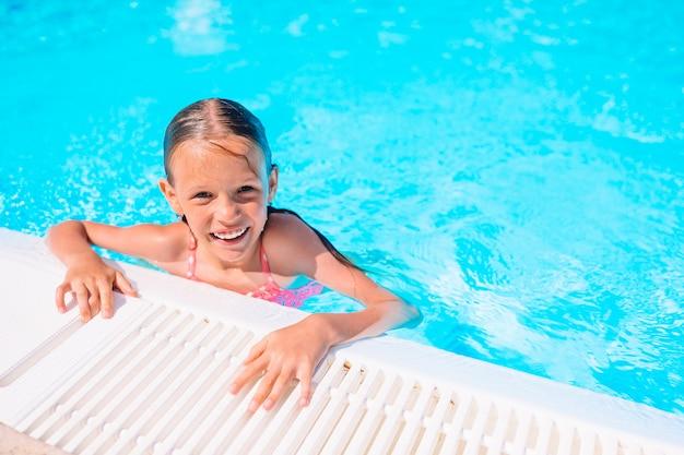 Entzückende schwimmen des kleinen mädchens swimmingpool am im freien