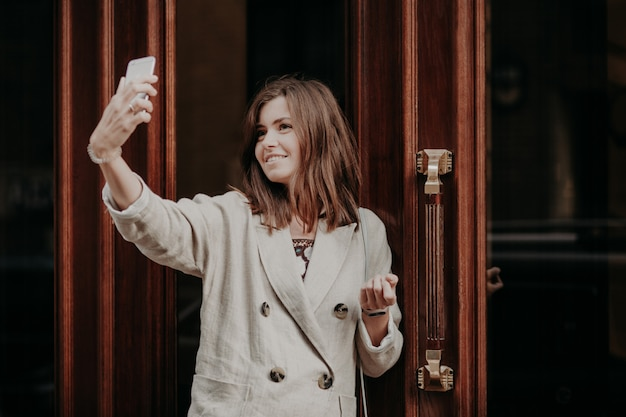 Entzückende studentin wirft für die herstellung von selfie auf, benutzt den modernen handy, gekleidet in der weißen jacke