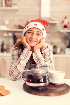 Entzückende teenager-mädchen mit weihnachtsmütze feiert weihnachten
