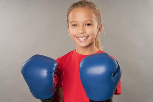 Entzückende weibliche kinderboxerin, die boxhandschuhe und rotes hemd trägt, während sie in die kamera schaut und lächelt