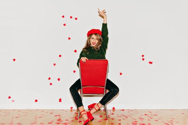 Entzückende weiße frau, die auf rotem stuhl mit hand oben sitzt