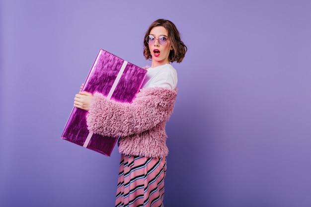 Entzückende weiße junge frau, die auf lila wand mit funkelnder geschenkbox aufwirft. geburtstagskind mit überraschtem gesichtsausdruck, der ihr geschenk hält.