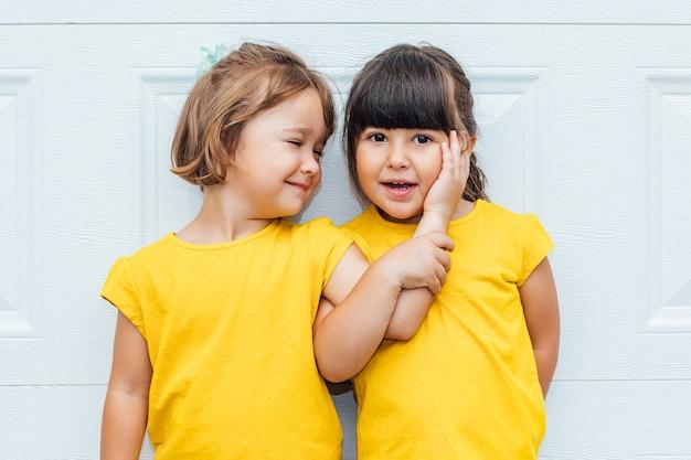 Entzückende zwillingsmädchen, die ein gelbes hemd tragen, das gegen weißen hintergrund lehnt