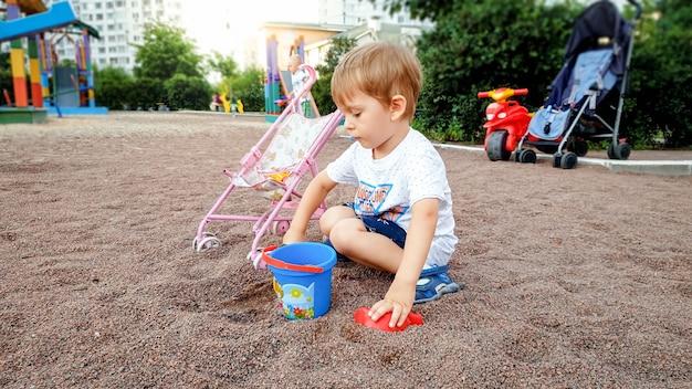 Entzückender 3-jähriger kleinkindjunge, der im sandkasten mit buntem plastikspielzeug spielt