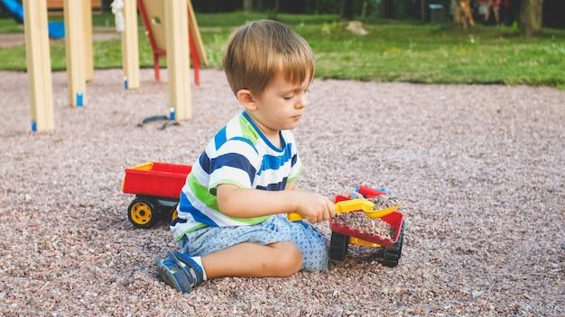 Entzückender 3-jähriger kleinkindjunge, der mit sand spielt und sie lkw und anhänger im park