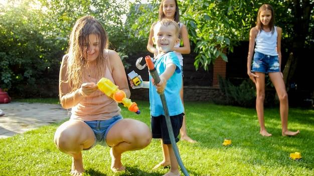 Entzückender 3 jahre alter kleinkindjunge, der wasser aus einer plastikspielzeugpistole im hinterhof des hauses spritzt. kinder, die im sommer im freien spielen und spaß haben