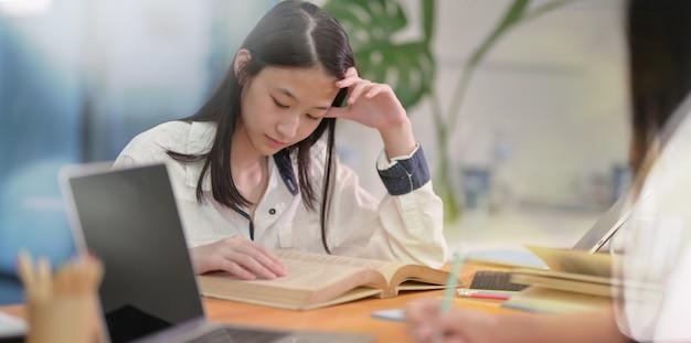 Entzückender asiatischer junger jugendlicher, der mit freund studiert