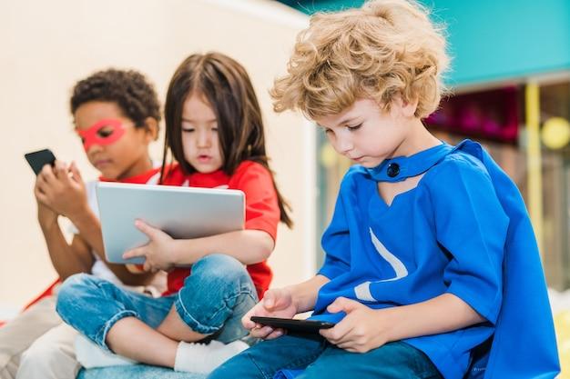 Entzückender blonder junge im kostüm des übermenschen, der im smartphone scrollt oder online-spiel mit seinen freunden auf hintergrund spielt
